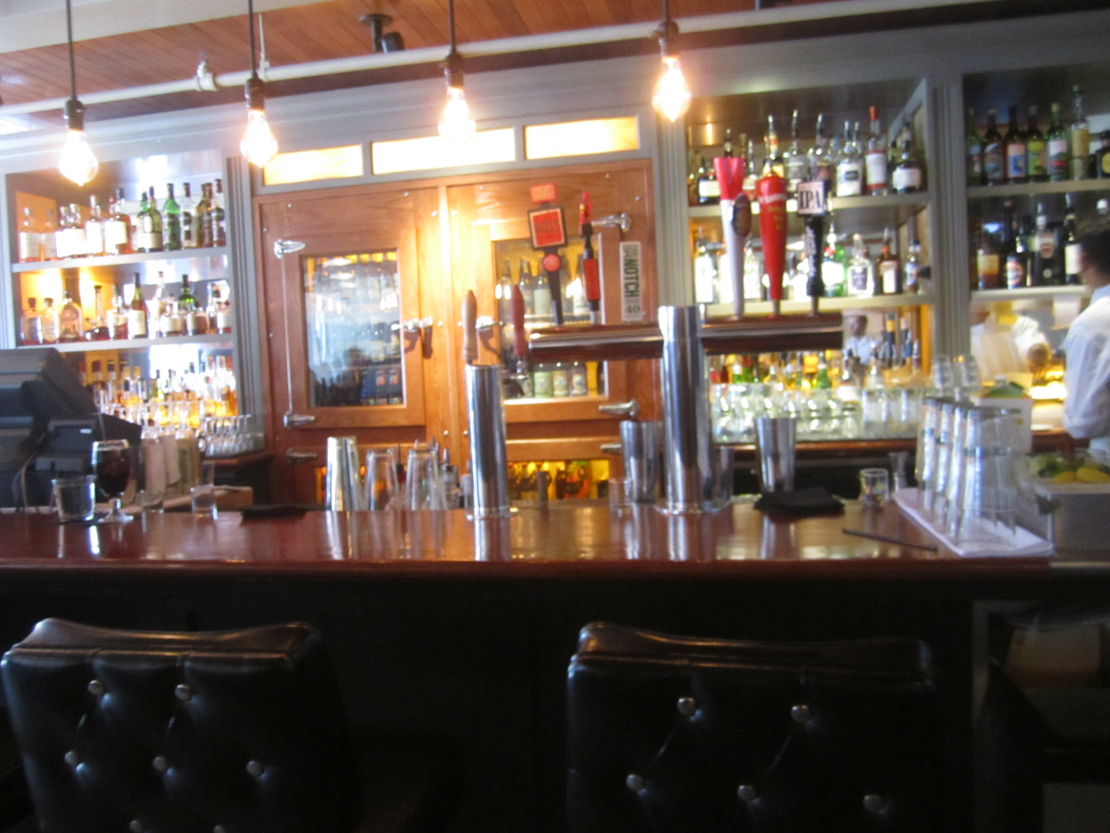 The Main Bar Area Is Warm With Luxurious Black Bar Stools.